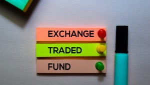 """close-up of the phrase """"exchange traded fund"""" on three colorful papers pinned to a wall by colorful pushpins"""