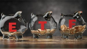 An image of three glass piggy banks with ETF written on the sides on a table.