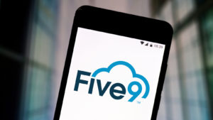 photo illustration of the Five9 logo seen displayed on a smartphone