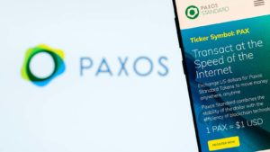 The website for the Paxos (PAX) crypto displayed in front of a logo background.