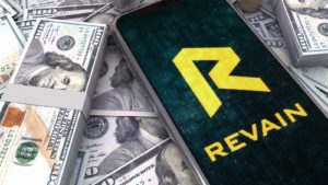 The logo for Revain (REV) displayed on a smartphone screen with stacks of cash in the backround.