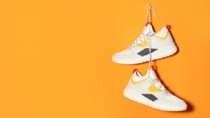 Photo de chaussures blanches avec des couleurs d'accent rouge et jaune accroché par des lacets attachés sur un clou sur un fond jaune