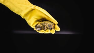 CCJ Stock: Hand in long yellow glove holding a chunk of uranium material