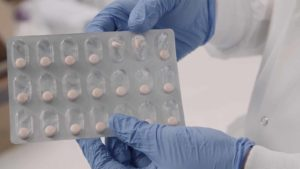 A photo of a person with gloves holding a pack of pills.
