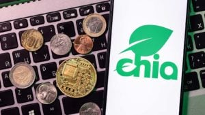 The logo for Chia (XCH) on a smartphone with crypto coins and a laptop keyboard in the background.