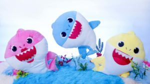 Pink, blue and yellow stuffed animals of baby sharks.