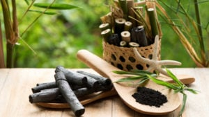 A basket of bamboo charcoal and a paddle of bamboo charcoal powder are on a table in an outdoor environment.