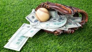 Un gant de baseball repose sur un terrain avec une balle de baseball et plusieurs billets de plusieurs centaines de dollars à l'intérieur.