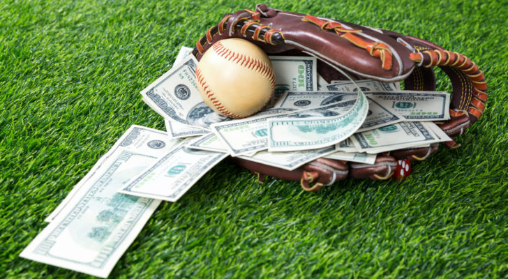 A baseball glove rests on a field with a baseball and several hundred dollar bills inside.