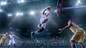 A basketball player makes a slam dunk in a crowded arena representing SBET stock.