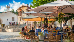 Several people are seated at a street cafe in Omodos, Cyprus.