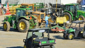 Several John Deere vehicles are parked outside of a building.