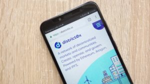 The logo for District0x (DNT-USD) displayed on a smartphone screen with a wooden background.