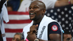 A close-up shot of Floyd Mayweather Jr. in front of an American flag.