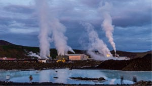 A geothermal power plant operates, with a large lake visible in the foreground and mountainous terrain visible in the background.
