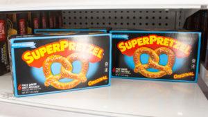 Several boxes of SuperPretzel brand pretzels from J&J Snack Foods are on a store shelf.