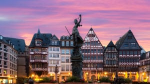 The statue of Lady Justice in Frankfurt, Germany is centered with buildings lit up behind in dusk.