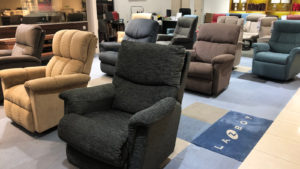 Several upholstered recliners are on display in a La-Z-Boy furniture store.