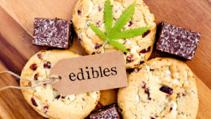 Several marijuana cookies and brownies are on a wood surface with a marijuana leaf and a tag with the word 'edibles' resting on top.