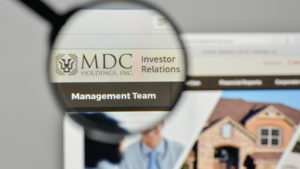 A magnifying glass is focused on the logo for MDC Holdings on the company's website.