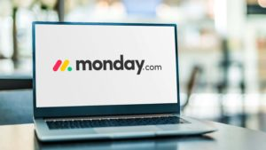 The Monday.com (MNDY) logo is displayed on a laptop screen.