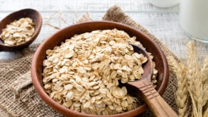 otly stock Rolled oats or oat flakes in bowl with wooden spoons