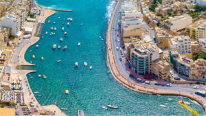 An aerial shot of Spinola Bay in Malta with numerous boats in the bay.
