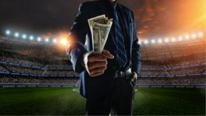 Une personne portant un costume et une cravate tient une poignée de billets d'un dollar au milieu d'un stade de sport bien éclairé.