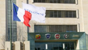 A flag with the logo for Stellantis waves outside a building with the logos for some of its car brands, including Abarth, Lancia, Fiat, Alfa Romeo and Jeep.