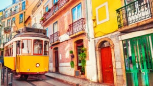 A yellow streetcar, or tram, operates on the street in Lisbon, Portugal.
