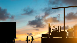 silhouettes of a forklift and driver as well as two workers by a semi truck backdropped by a sunset sky. represents the supply chain