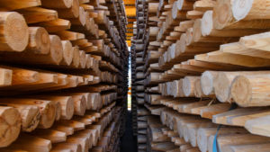 photo of walking space between two very tall stacks of processed timber