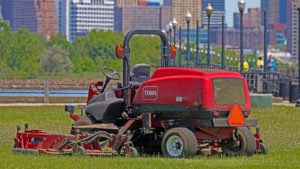A Toro Groundmaster 5900 ride-on lawnmower sits in a field with skyscrapers visible in the background.