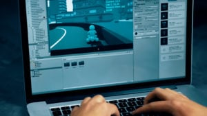 A developer works on a 3D racing game in the Unity engine on a laptop.
