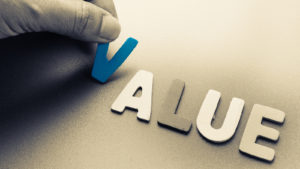 """Value stocks: A hand places wooden cutouts of the letters in the word """"value"""" on a surface."""