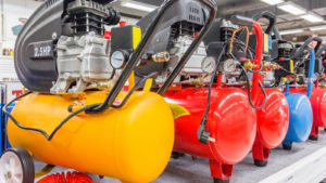 A row of yellow, red and blue air compressors are lined up next to each other.
