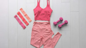 A pink athleisure outfit is laid out on a floor next to a pair of dumbbells.