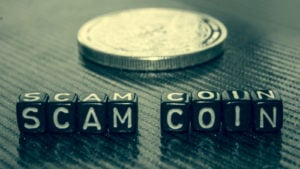 """""""Scam coin"""" spelled out on blocks in front of a crypto token."""
