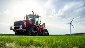 IDEX stock: An electric tractor sits in a field on a sunny day with a wind turbine in the background.