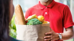 A person receives a delivery of groceries in a paper bag from other person.