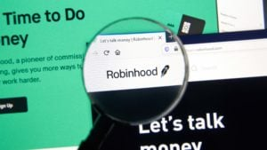A magnifying glass zooms in on the website for Robinhood (HOOD).