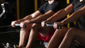 Two people use indoor rowing machines next to each other.