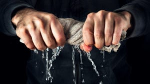 Man squeezing water out of a rag representing ZIVO Stock.