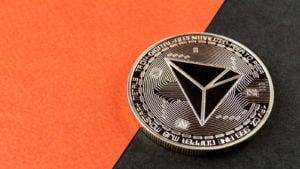 cryptos: a TRON (TRX) concept coin against an orange and black background