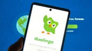 DUOL stock: A phone displaying the duolingo logo in front of a computer screen displaying the duolingo site