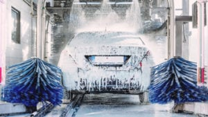 new stocks MCW stock: a car covered in soap going through an automated car wash