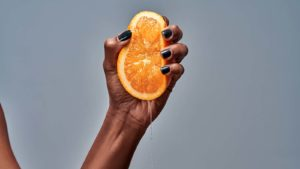 A hand with black nail polish squeezing an orange in front of a grey background.