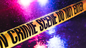 """Yellow tape reading """"crime scene do not enter"""" is stretched across a rainy, night time setting."""