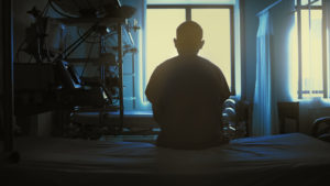 A person in silhouette faces toward a bright window while sitting at the edge of a hospital bed.