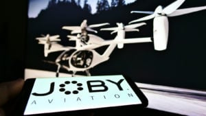Person holding smartphone with logo of startup and aerospace company Joby Aviation (air taxi) on screen